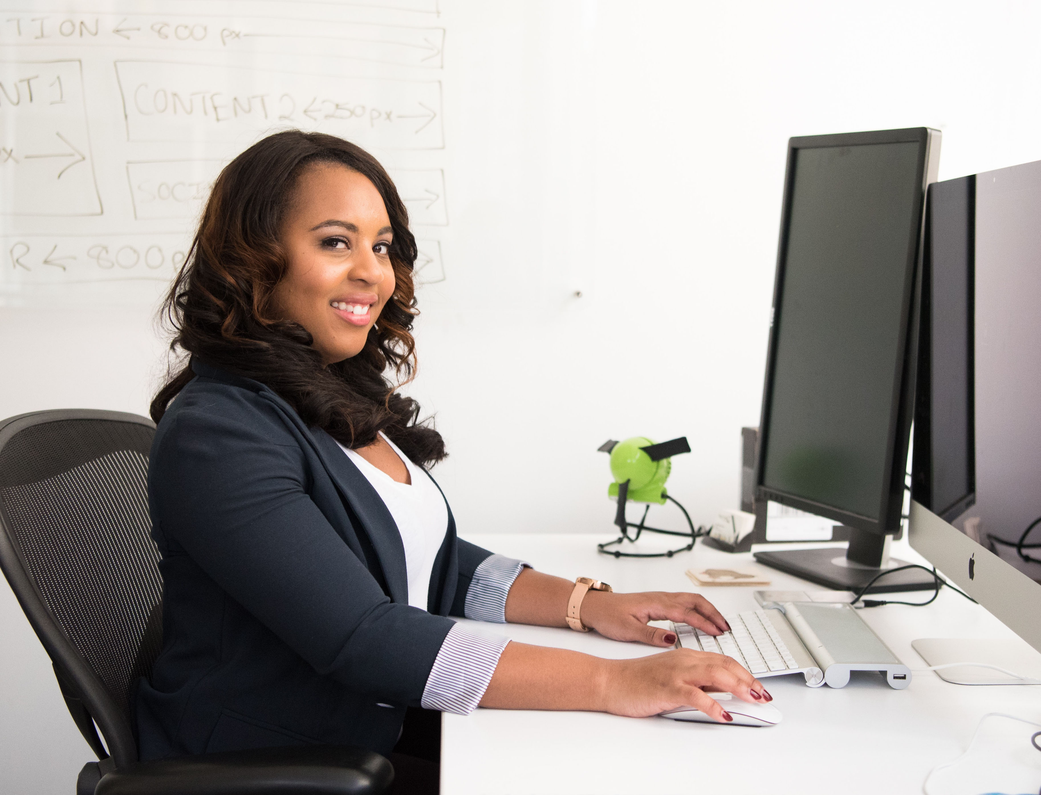 Woman wearing black cardigan sitting on her office